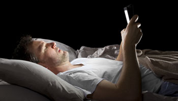 Man reading his phone in bed to try and go to sleep